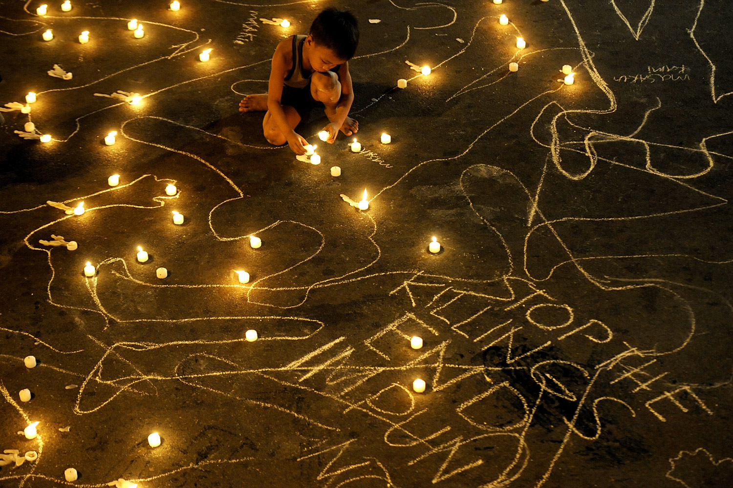 November 23, 2011. A boy lights a candle during a vigil to commemorate the second anniversary of the Maguindanao massacre, near the Malacanang palace in Manila. Relatives of 57 people killed in the Philippines' worst political massacre called on authorities to speed up the suspects' trial as they marked the second anniversary of the murders.