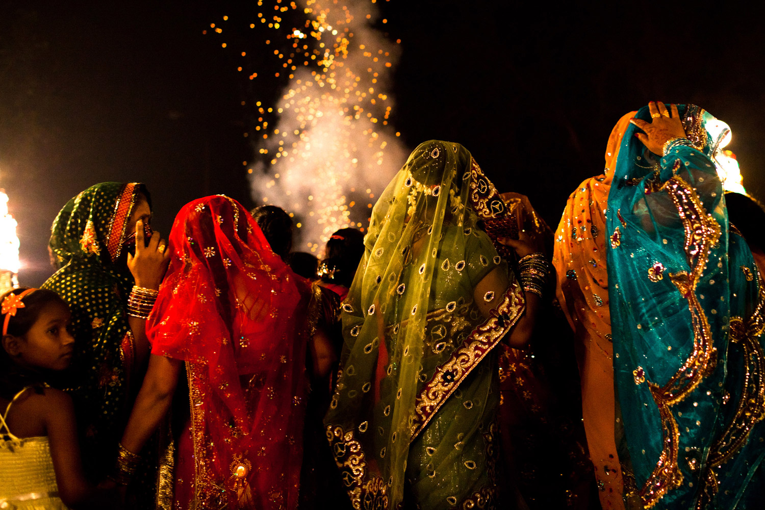 November 23, 2011. A girl looks on as women dressed in saris accompany a wedding procession in New Delhi, India. India's wedding season peaks from late October to early December each year as couples choose to wed in these auspicious months. The Indian wedding traditionally starts with a procession which sees the groom riding or drawn by a carriage with a white horse, escorted by close family and friends, a brass band and a mobile lighting crew powered by a diesel generator. Guests in attendance dance and celebrate through the streets, showering the groom with rupee notes, until they arrive to the final destination of the wedding.