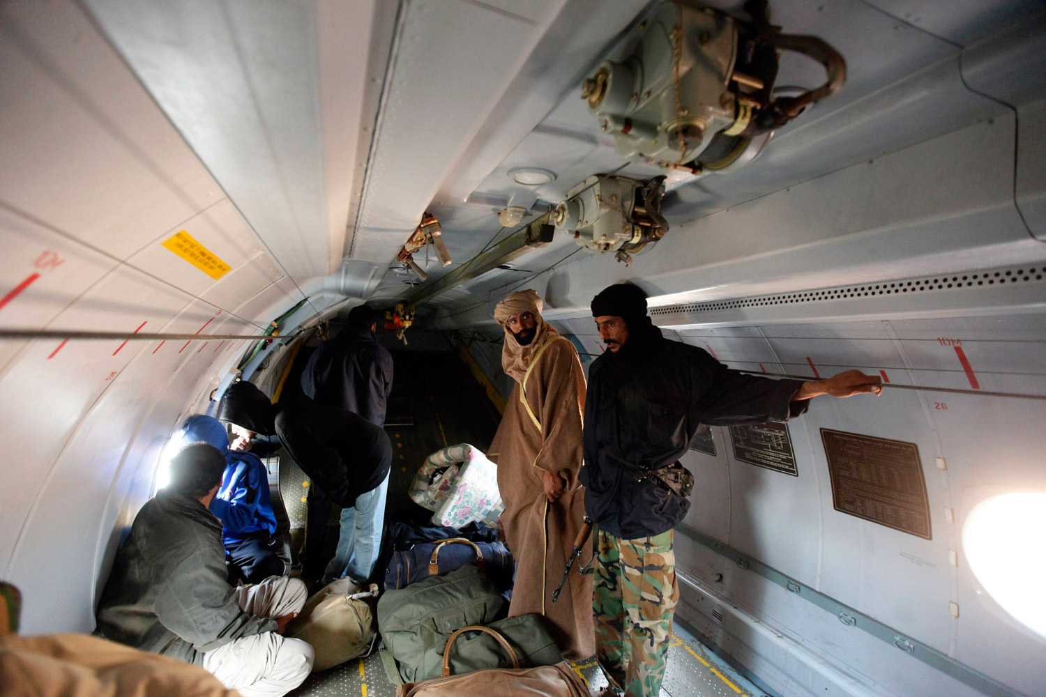 November 19, 2011. Saif al-Islam Gaddafi (second right) is pictured standing in a plane in Zintan. Saif al-Islam Gaddafi told Reuters that he was feeling fine after being captured by some of the fighters who overthrew his father and suffering injuries to his right hand during a NATO air strike a month ago.