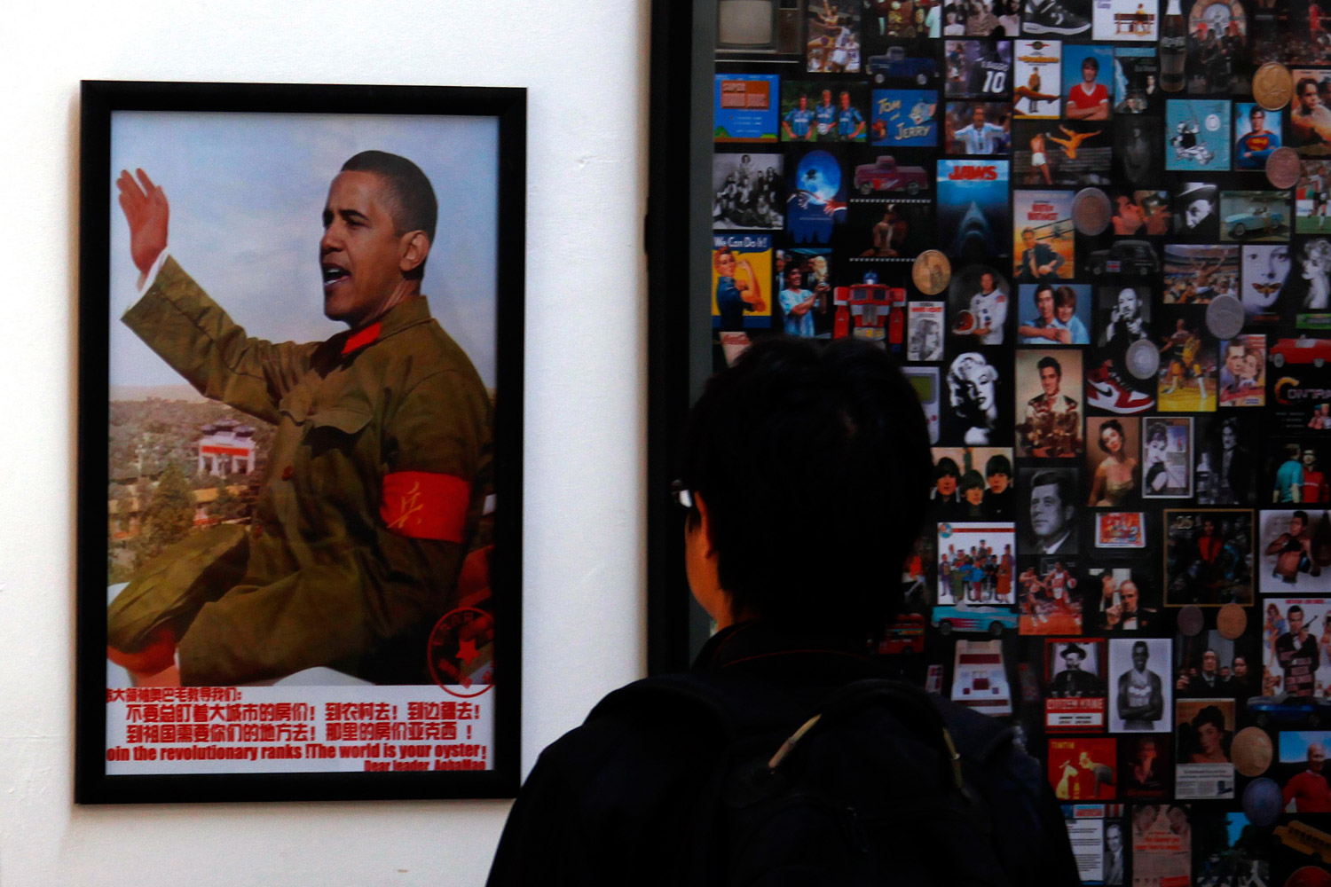 November 21, 2011. A visitor to a gallery located in the art district of Beijing known as '798' looks at a work on display showing the head of U.S. President Barack Obama superimposed onto the body of former Chinese chairman Mao Zedong.