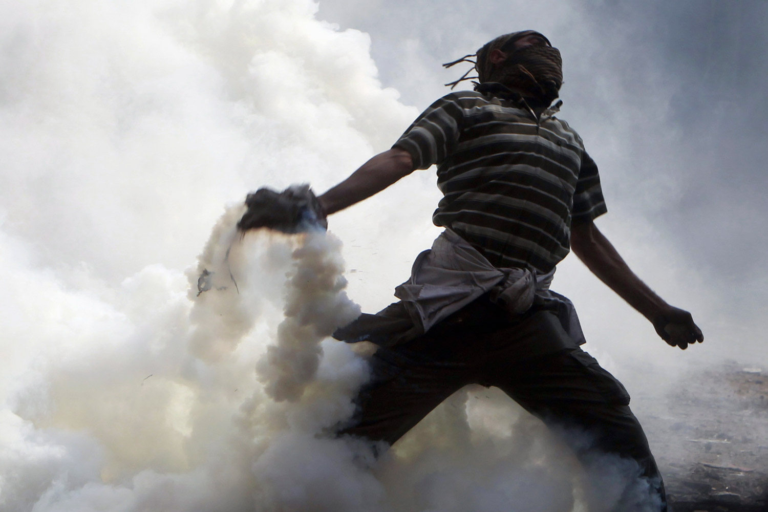 November 22, 2011. A protester tosses a tear gas canister, which was earlier thrown by riot police during clashes along a road which leads to the Interior Ministry, near Tahrir Square in Cairo. Egyptians frustrated with military rule battled police in the streets again on Nov. 22 as generals scrambled to cope with the cabinet's proffered resignation after bloodshed that has jolted plans for Egypt's first free election in decades.