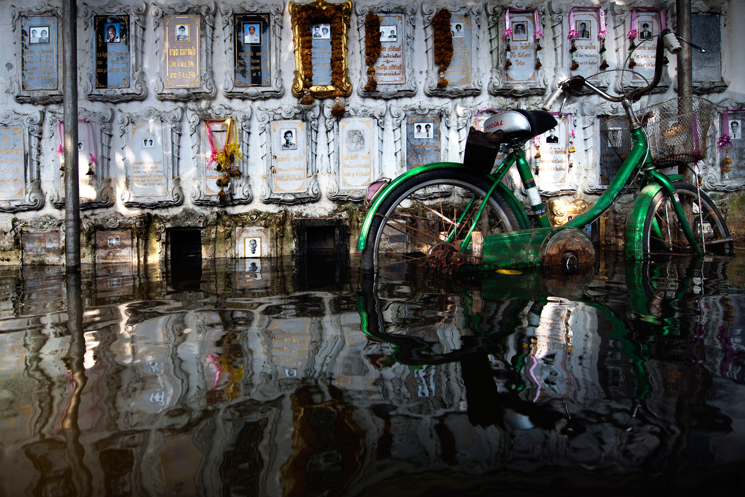 November 18, 2011. A bicycle leans against the tombstones in a flooded temple in Dong Muaeng area. Severe flooding since October, which has left hundreds of people dead, has also hurt a wide range of industries in the production hub, particularly the automotive and computer hard-disk drive sectors. The consequences have been global, hitting large number of international companies. Thailand has experiencing the worst floods in 50 years.