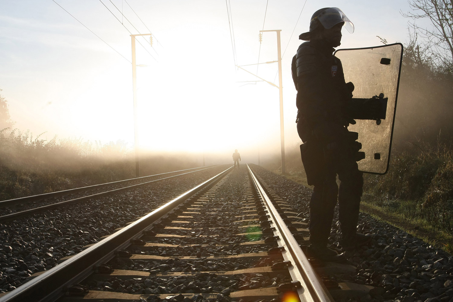 November 23, 2011. Riot police officers secure the railway tracks in Lieusaint, Normandy, France, as environmental activists try to block the train line in an effort to stop a train loaded with nuclear waste and heading to Gorleben in Germany.