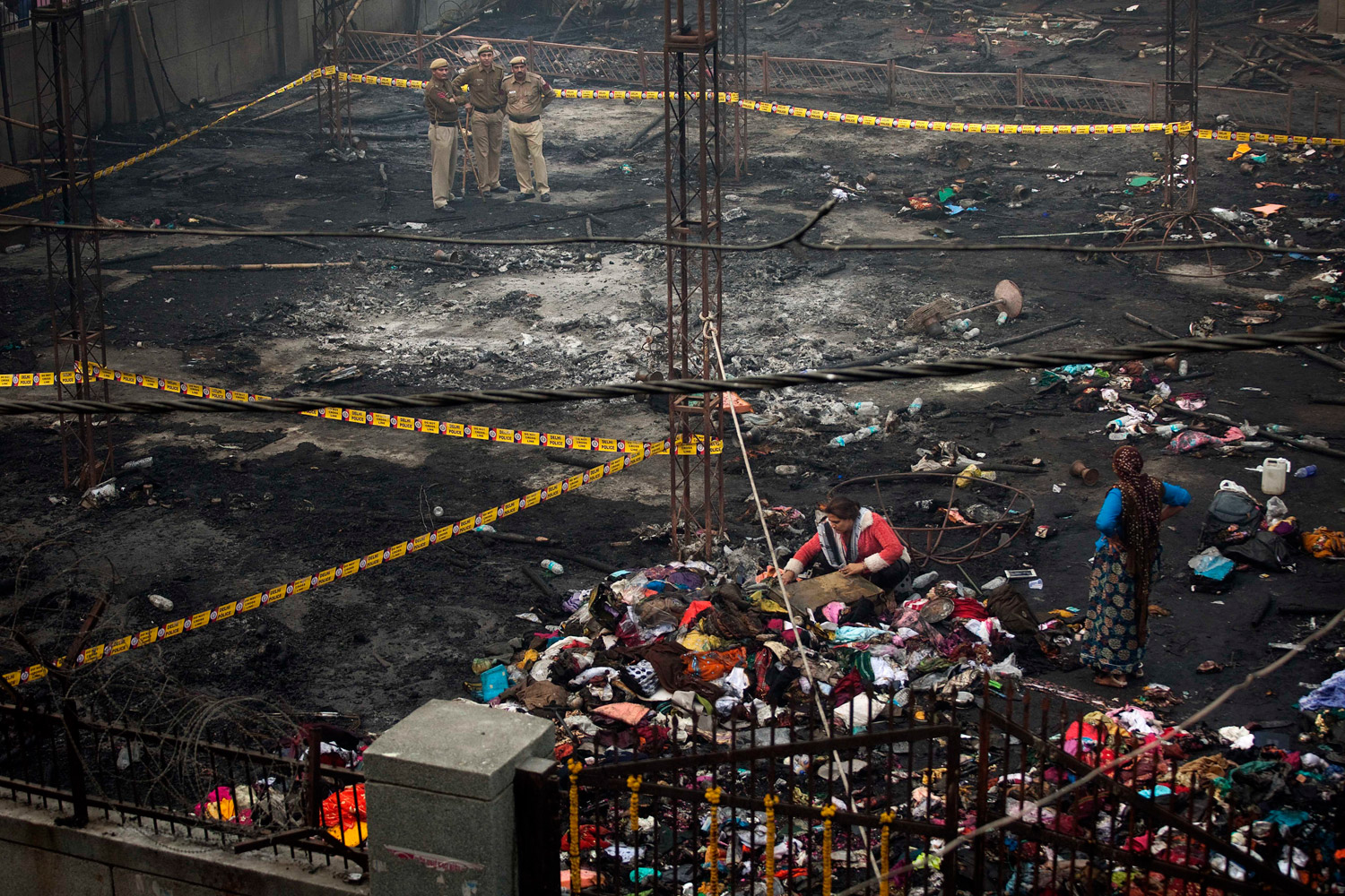 November 21, 2011. Police officers guard the scene as an Indian eunuch looks for valuables at the scene of a fire in New Delhi, India. The blaze, which killed more than a dozen people, happened during a gathering of thousands of eunuchs at a prayer ceremony and feast held once every five years at a fairground in the Nandnagary neighborhood of east Delhi.