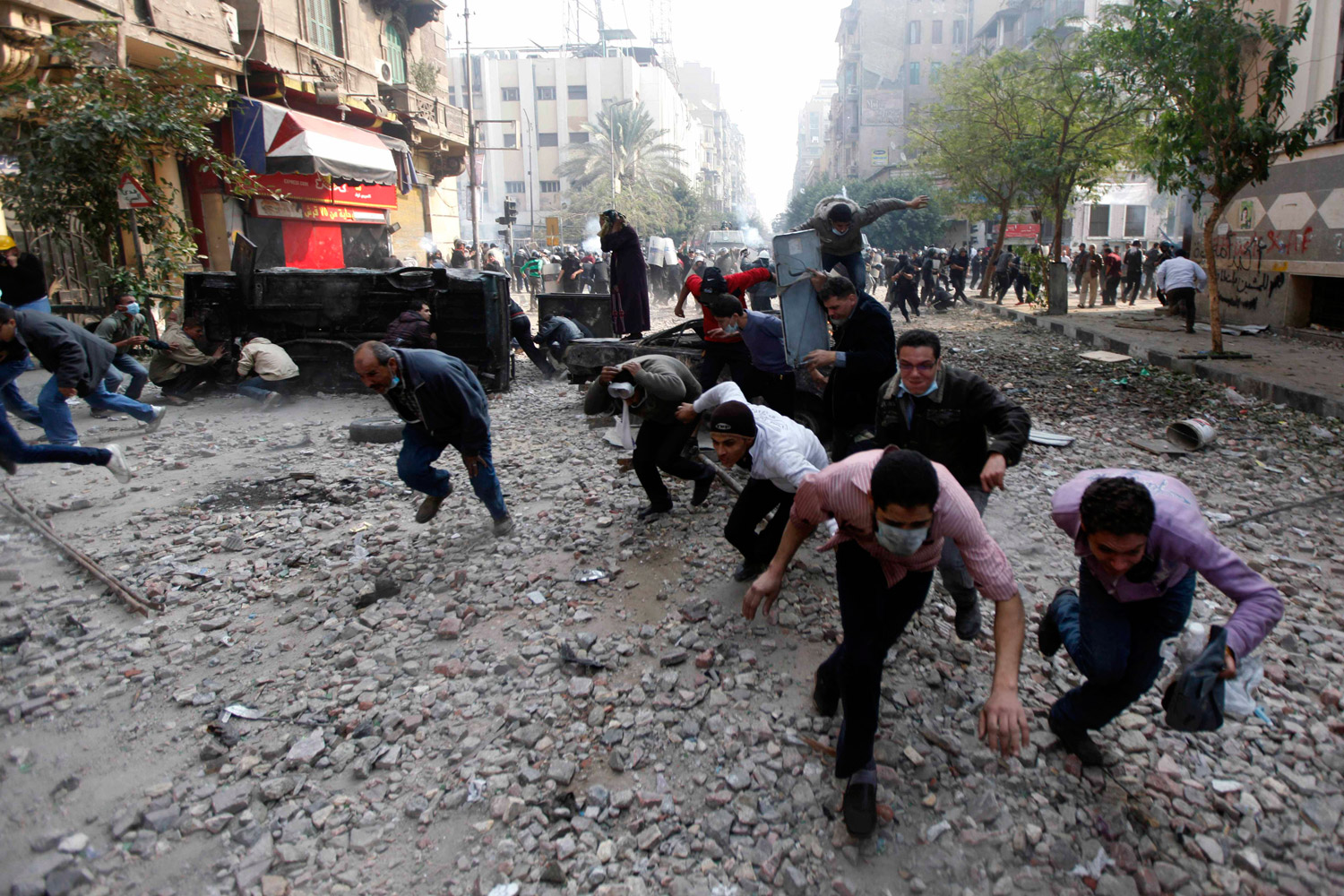 November 22, 2011. Protesters run for cover during clashes with the Egyptian riot police near Tahrir square in Cairo, Egypt.