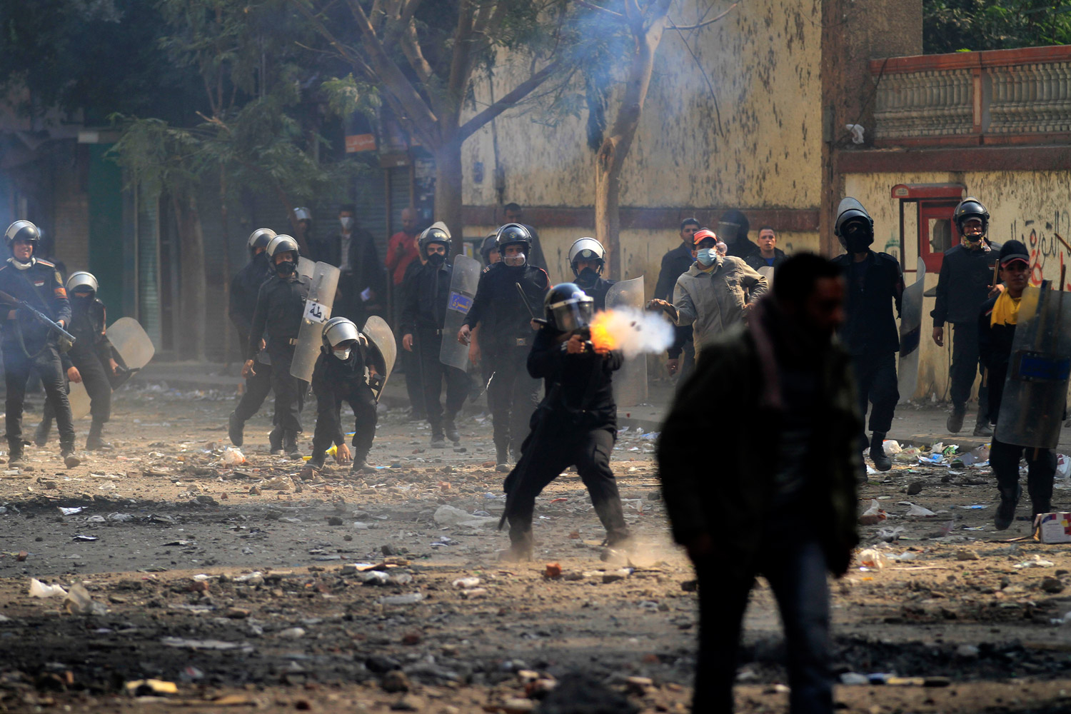 November 22, 2011. An Egyptian riot police officer fires tear gas during clashes with protesters near Tahrir square in Cairo, Egypt. Egypt's civilian cabinet had offered to resign after three days of violent clashes in many cities between demonstrators and security forces, but the action failed to satisfy protesters deeply frustrated with the new military rulers.