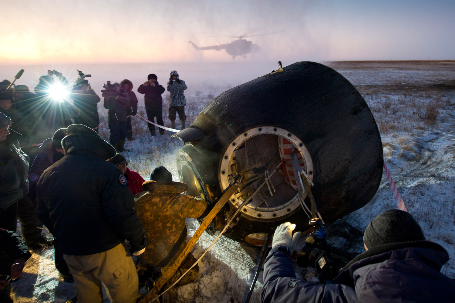 November 22, 2011. Russian support personnel work to get crew members out of the Soyuz TMA-02M re-entry module after the capsule landed in a remote area of Kazakhstan. The crew was returning from more than five months aboard the International Space Station.