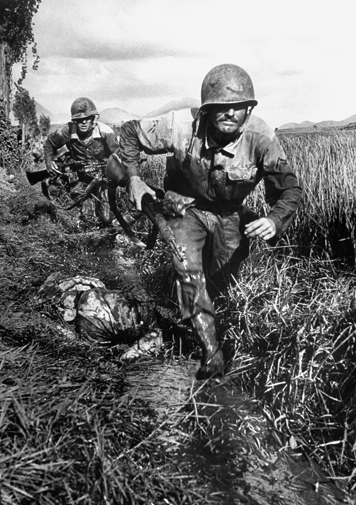 Two U.S. Marines of Co. B, 1st Brigade, 5th Regiment grimly advancing along a ditch past an enemy corpse during the fighting in the Naktong River area in August 1950.