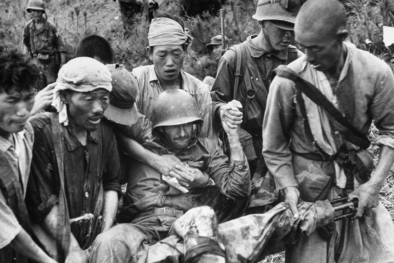 Korean medical aides carrying a wounded U.S. Marine from the 5th Marine Regiment from battlefield during UN forces' fight against North Koreans along Naktong River; the Marines fought to hold the Pusan perimeter at the start of Korean War in August 1950.