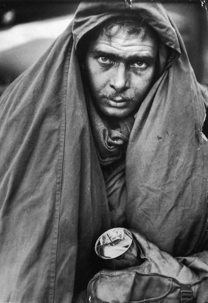 A weary, exhausted Marine wrapping himself in a sleeping bag against the cold and clutching a can of food during a retreat from fierce fighting around the Changjin Reservoir in December 1950.