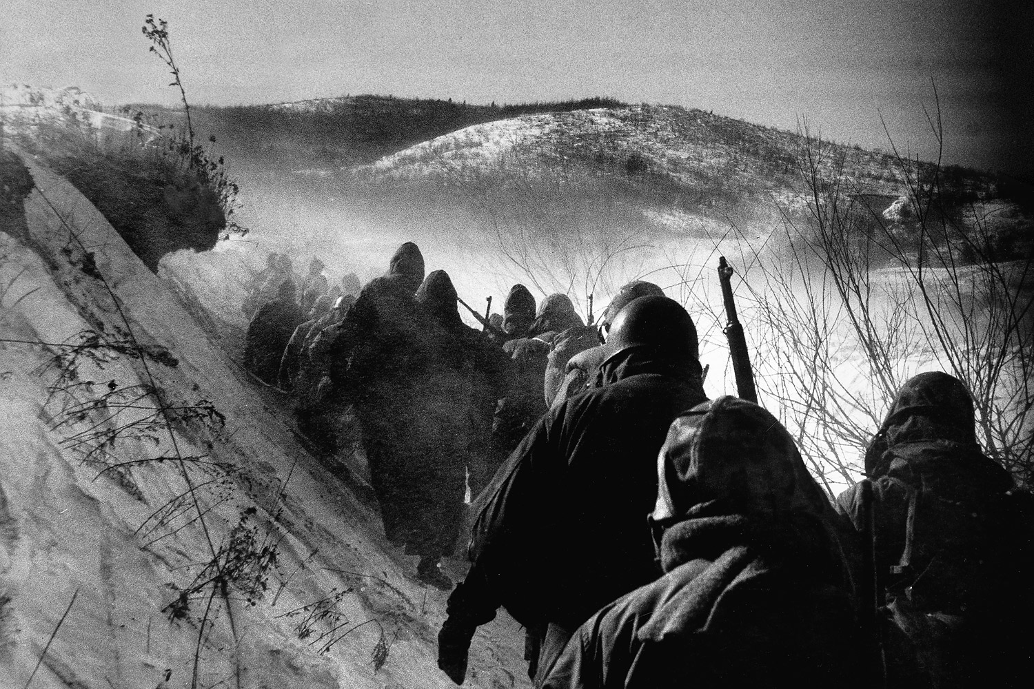 U.S. Marines of the 1st Division marching in a long column down canyon road they called  Nightmare Alley  during their grim retreat from the Changjin Reservoir towards Hamhung after being cut off by the Red Chinese in December 1950.