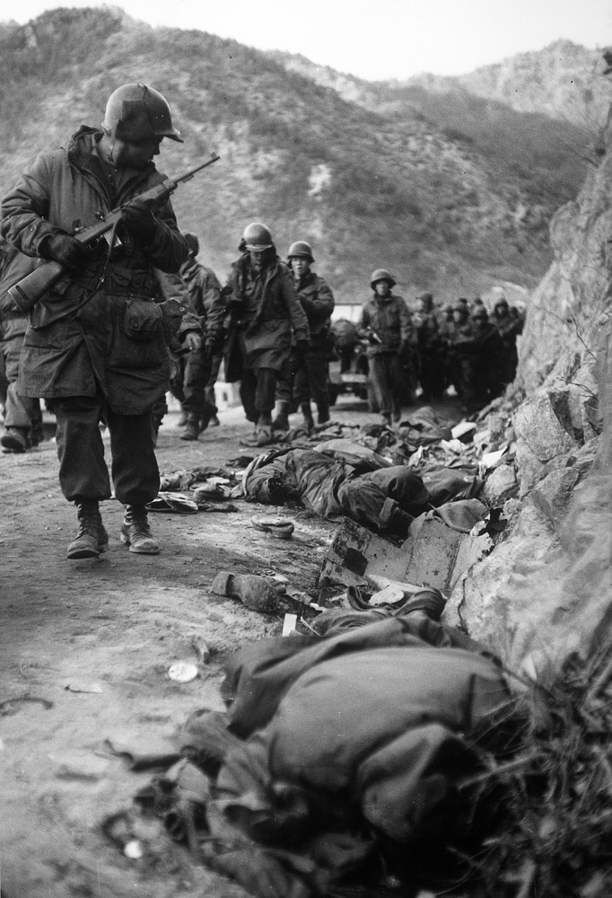 U.S. Marines passing bodies of fallen comrades during the grim retreat from the Changjin Reservoir after being cut off by a surprise attack by Chinese troops during the Korean War in December 1950.