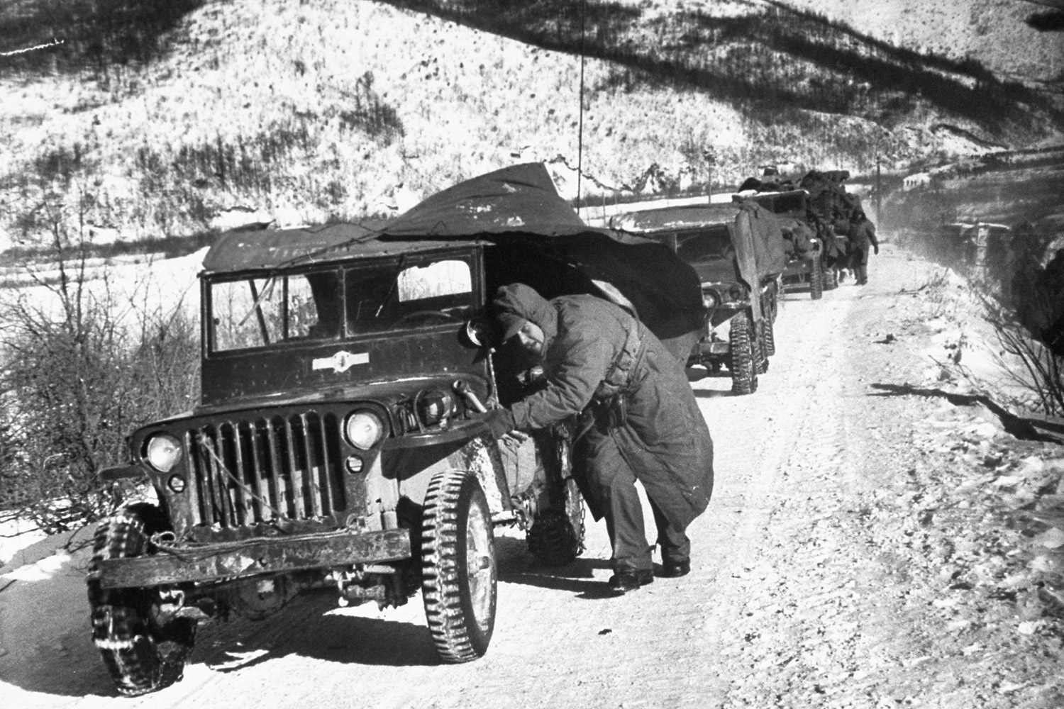 U.S. Marine crouching down next to his jeep while leading a convoy of vehicles during the 1st Marine Division's retreat down canyon road they called  Nightmare Alley,  after being cut off by the Red Chinese and under fire from nearby hills in December 1950.