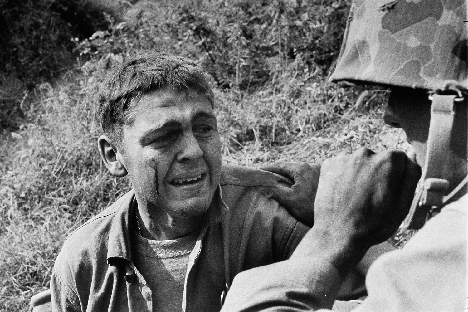 An upset young Marine is comforted after the jeep he was driving hit a landmine around the Naktong River in August 1950.