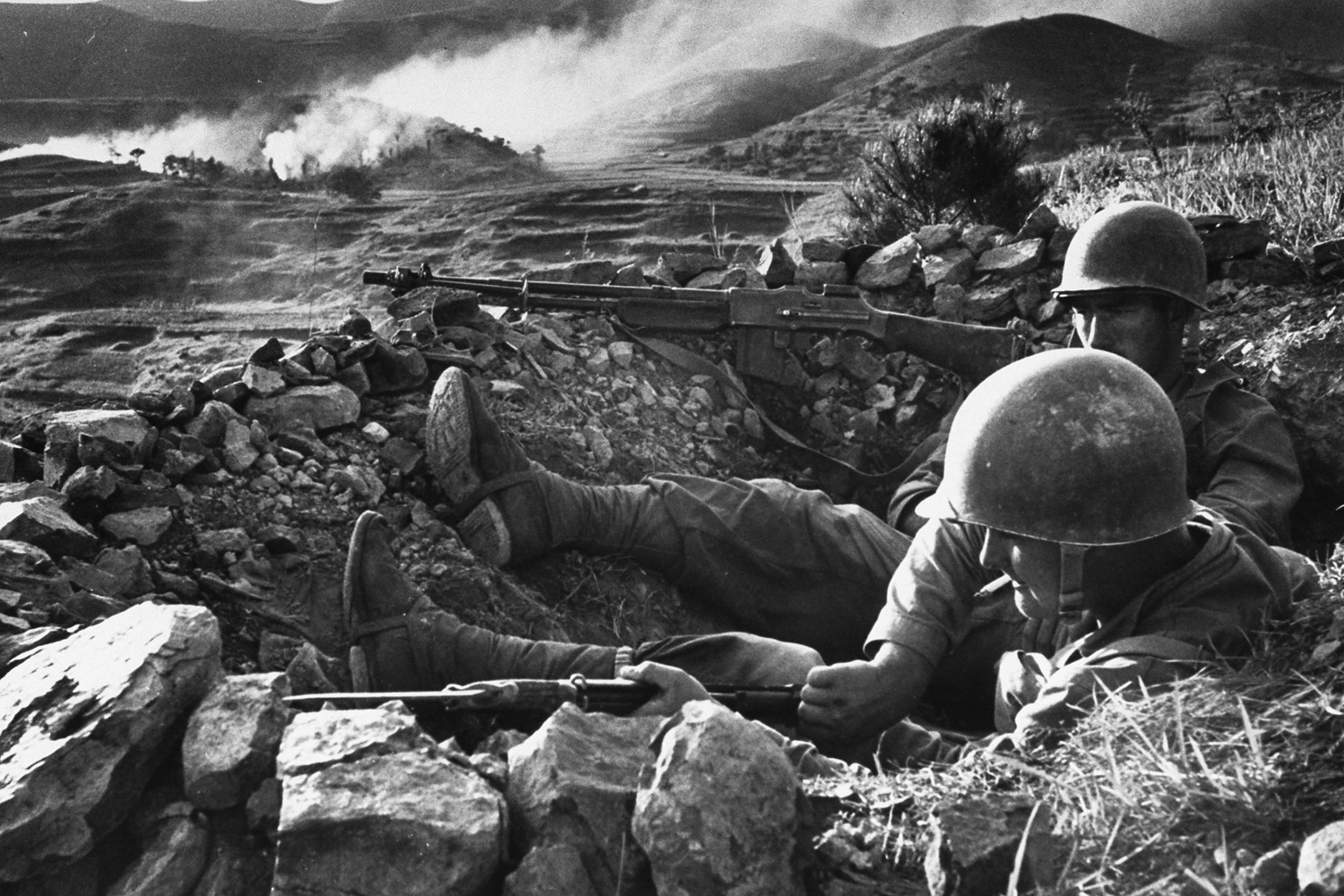U.S. Marines resting in a foxhole while awaiting a North Korean counterattack near the Naktong River in August 1950.