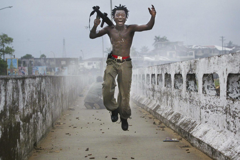 Chris Hondros' image of a Liberian militia commander's exultation after firing a rocket-propelled grenade at rebel forces at a key strategic bridge in Monrovia, Liberia on July 20, 2003.