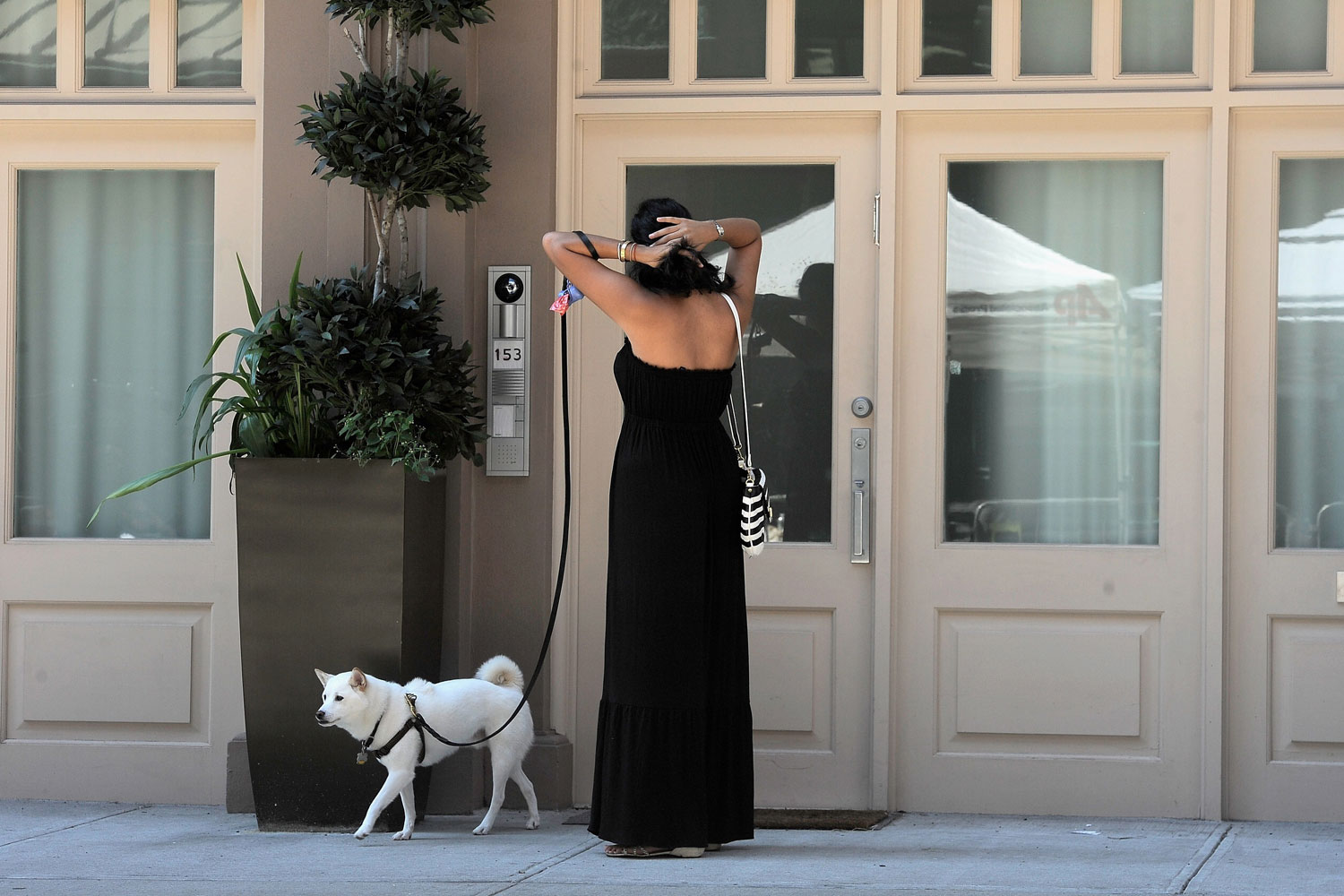 July 10, 2011. A female passerby adjust her hair using the glass in the front door of the  temporary residence of Dominique Strauss-Kahn and Anne Sinclair in the Tribeca neighborhood of New York City.