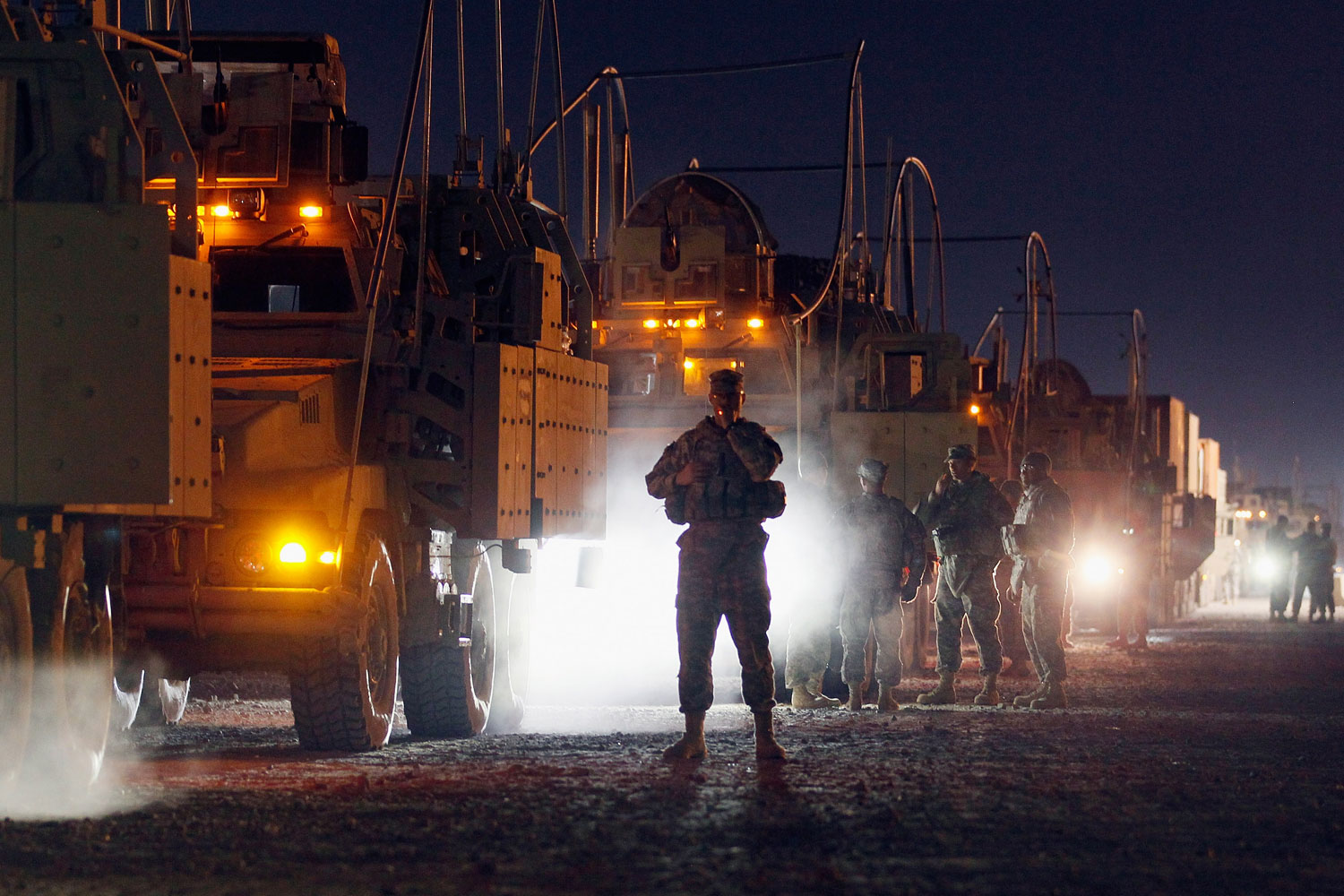 December 7, 2011. U.S. Army soldiers from the 2-82 Field Artillery, 3rd Brigade, 1st Cavalry Division, wait to load onto their armored vehicles as they prepare to convoy to Kuwait from Camp Adder in Iraq  at Camp Adder, near Nasiriyah, Iraq. After seven months in Iraq, the third Brigade is pulling out of the country as part of America's military exodus by the end of December after eight years of war and occupation which included the overthrow of Saddam Hussein.