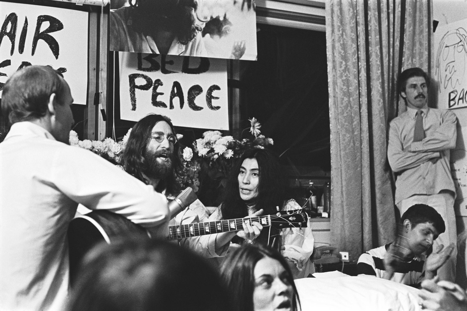 The couple sits among friends Tommy Smothers, far left, and Derek Taylor, standing far right, singing  Give Peace a Chance.