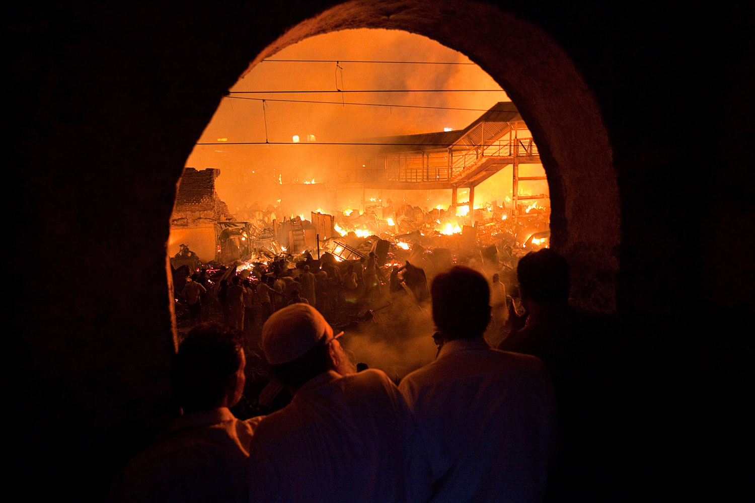 March 4, 2011. People watch from a nearby building as a fire burns in a slum in Mumbai. A fire gutted a large shanty town, home to hundreds of residents, next to Bandra station in Mumbai's suburbs.