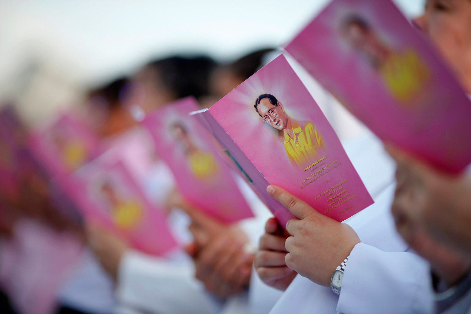 December 5, 2011. Catholic nuns hold booklets with pictures of Thailand's King Bhumibol Adulyadej as they sing outside the Royal Palace in Bangkok to mark his 84th birthday.