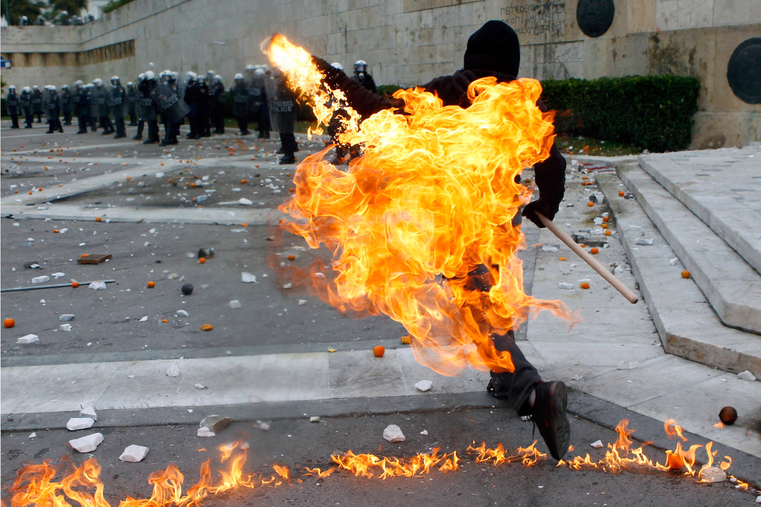 December 6, 2011. A protester hurls a petrol bomb toward riot police in Athens' Syntagma Square, the center of months of demonstrations in Greece. Activists were marking the anniversary of the 2008 shooting of a student by police.
