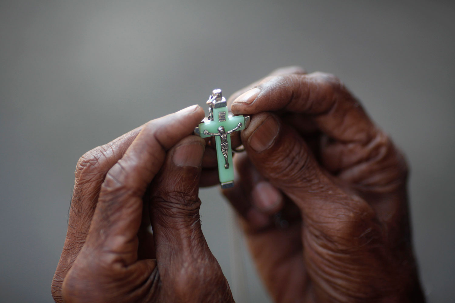 December 8, 2011. A man holds a cross as he prays during a ceremony to mark the 100th anniversary of of the founding of the St. Mary's Cathedral in Yangon.