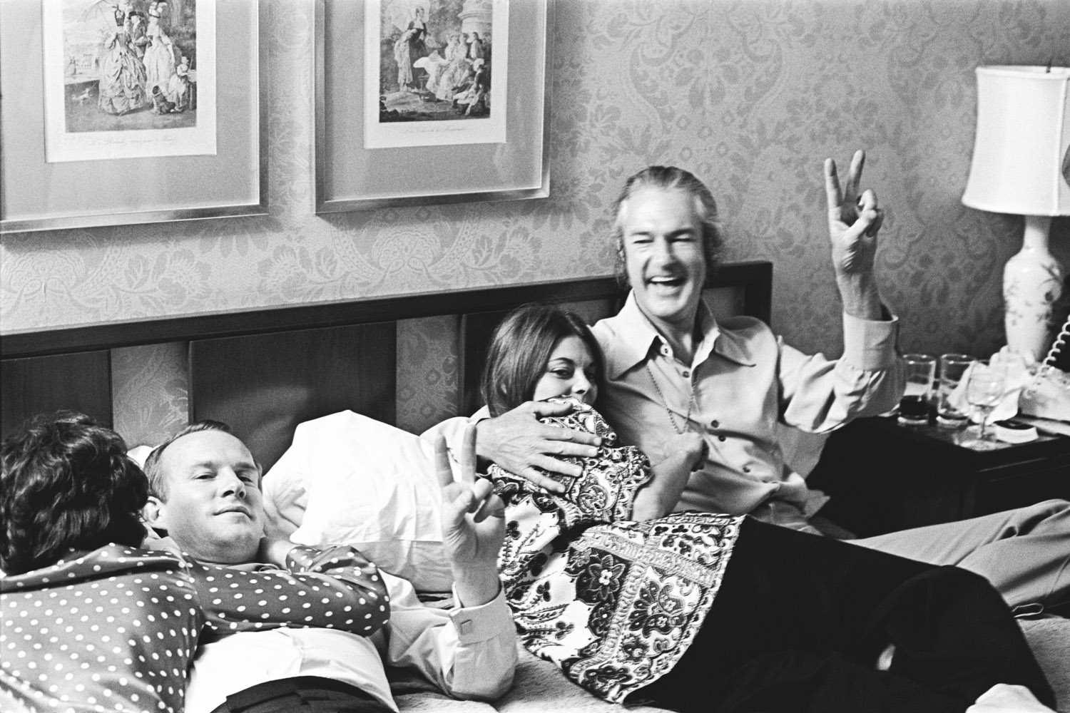 Tommy Smothers, with Rosemary and Timothy Leary, gives the peace sign.