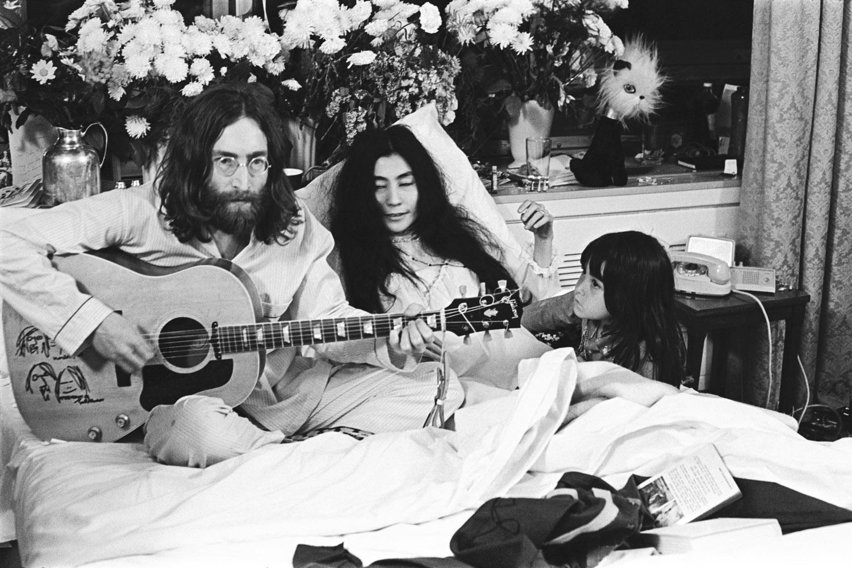 Kyoko Ono listens to John Lennon strum his guitar next to her mother, Yoko.