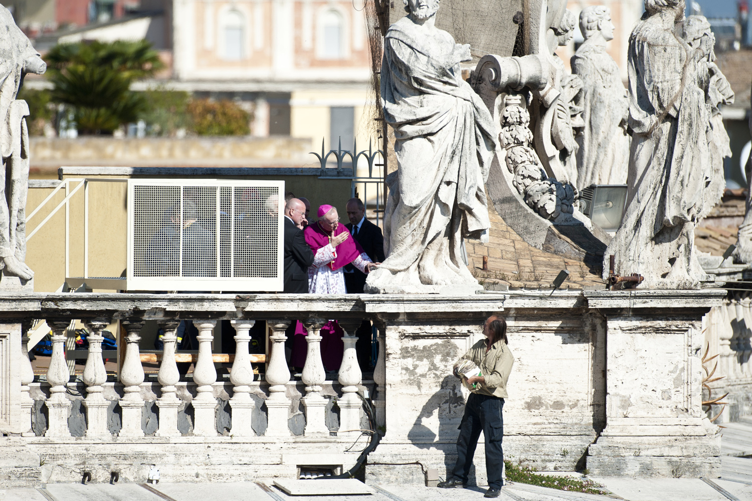 October 23, 2011. An unidentified man holds a copy of the Holy Bible as he stands on the edge of the colonnade that surrounds St. Peter's square at the Vatican, during a beatification Mass celebrated by Pope Benedict XVI.