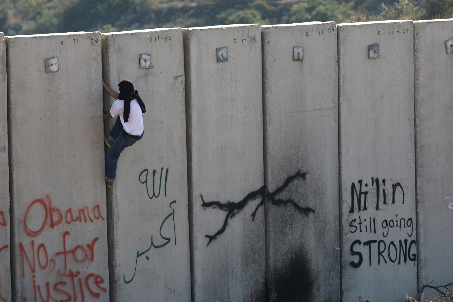 December 2, 2011. A Palestinian protester climbs Israel's separation wall during a weekly demonstration against Israeli occupation in the West Bank village of Nilin. While change sweeps the Arab world, little progress has been seen in the Israeli-Palestinian dispute.