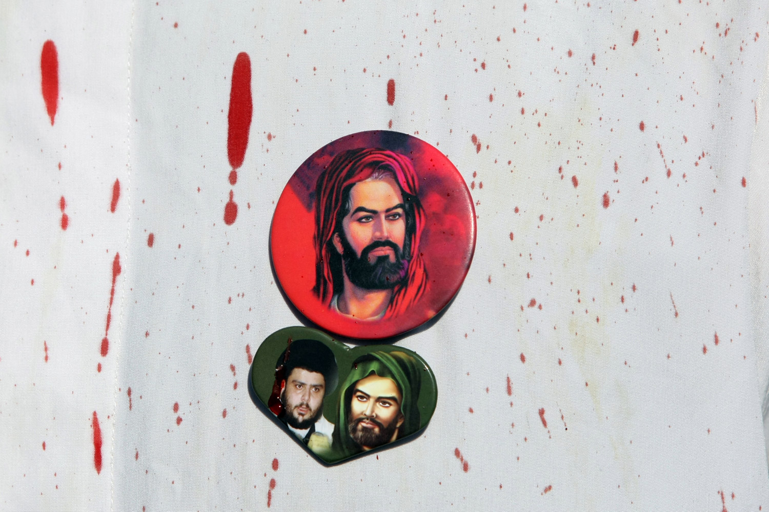 December 6, 2011. A badge picturing Imam Hussein, grandson of the Prophet Muhammad, and another of him with the Iraqi Shi'ite cleric Moqtada al‑Sadr, are seen on the bloodstained shirt of a man taking part in the Shi'ite commemoration of Ashura, a holiday marking Hussein's death that can involve ritual bloodletting.