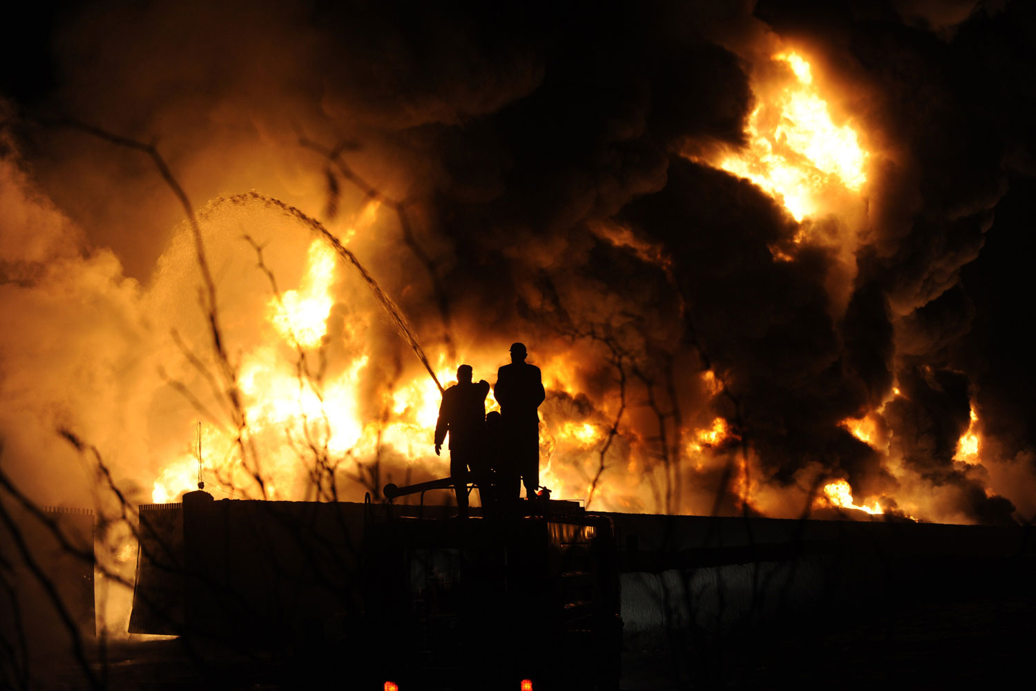 December 8, 2011. Pakistani firefighters extinguish burning NATO supply oil tankers and goods trucks at a terminal following an attack by gunmen in Quetta. Up to 20 trucks were ablaze after a rocket attack on a NATO trucking terminal in Quetta, the capital of the southwestern Pakistani province of Baluchistan, officials said.