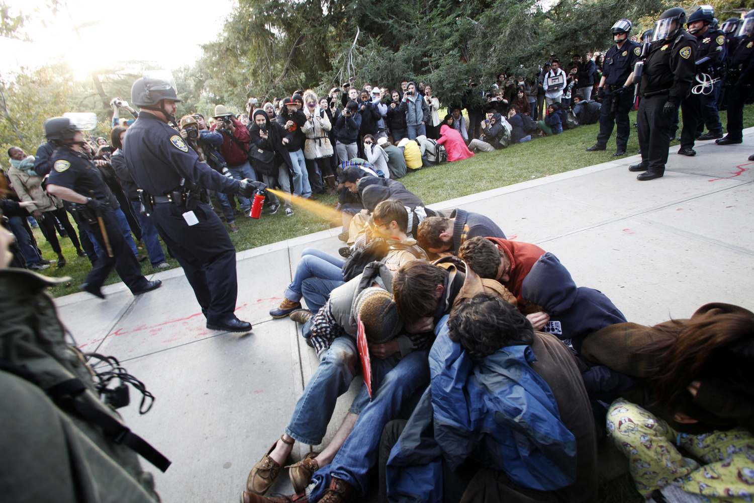 On Friday 18 November, Campus police at the University of California at Davis nonchalantly used pepper spray against students who sat peacefully on the school's quad to protest tuition increases. Online video and stills show the officers standing over the protesters and spraying them repeatedly at point blank range.  It was such an                               intense feeling. It felt like acid was being poured on our faces  said 21-year-old student Sophia Kamran who was among those targeted. Two officers involved in the incident were later placed on administrative leave—while a task force has been put together to address the incident and the results of a report are awaited.                                                              The episode at UC Davis followed controversial police deployments of pepper spray over the preceding days--- on 17 November against Occupy Portland participants in Pioneer Courthouse Square, and in another instance on 15 November when dozens of people including a pregnant woman and an 84-year-old activist were doused during the Occupy Seattle protests. Amidst much online debate, stills and footage in each case went viral--including this image from California by Wayne Tilcock. The YouTube video of the UC Davis incident alone reached more than 1.3 million views that weekend--while a number of creative and humorous reworkings of the images were also widely shared online.