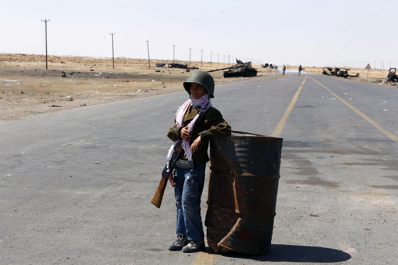 April 13, 2011. Mohamed, 10, stands guard at the frontline along the western entrance of Ajdabiyah, Libya.