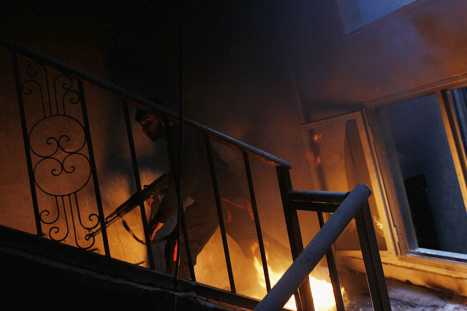 April 20, 2011. Chris Hondros photographed a rebel fighter braving a burning stairwell in pursuit of government troops while ensconced in a building on Tripoli Street in Misrata, Libya, on April 20. Later that day, Hondros and photographer Tim Hetherington were killed while covering the battle between the rebels and Gaddafi loyalists.