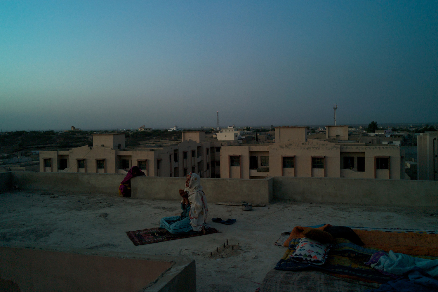 April 22, 2011.  A woman says maghreb prayers on the rooftop of Karachi's Labour Square Flats in Pakistan.