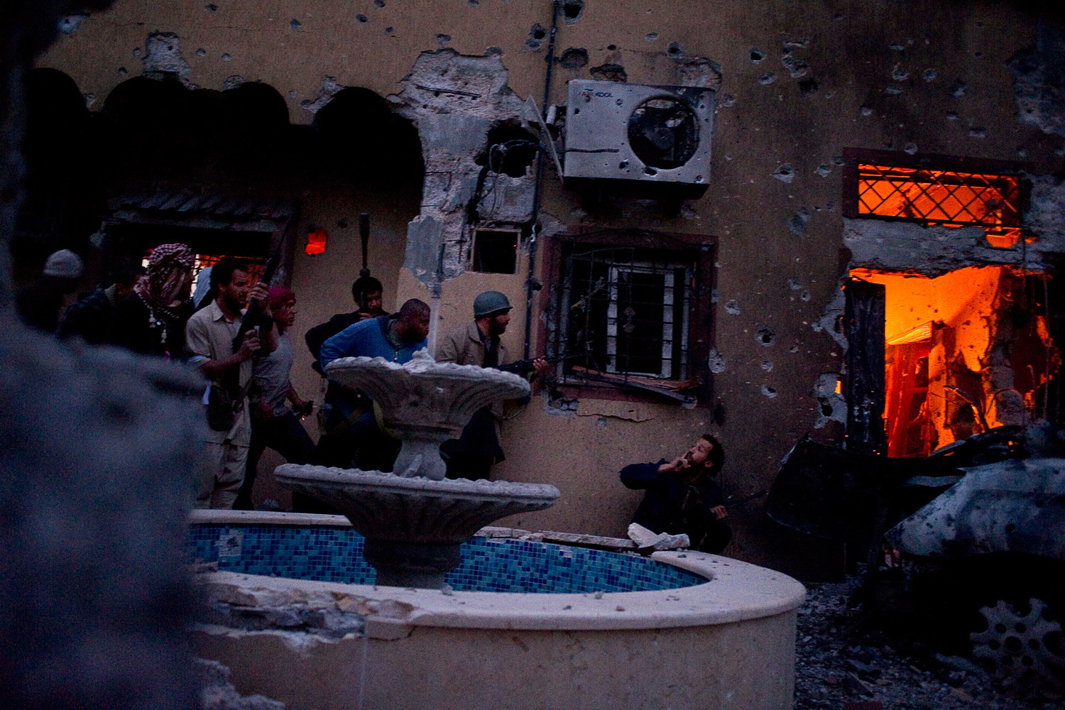 April 24, 2011. Rebels invade a house that served as a base for pro-government forces in the western city of Misrata, Libya.