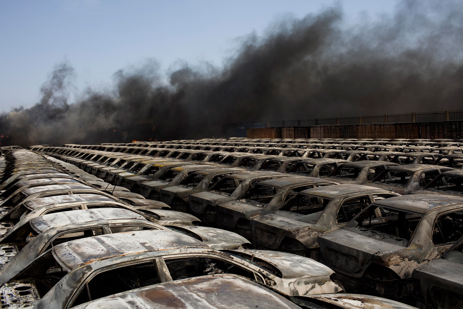 April 27, 2011. Burned cars are seen next a plume of black smoke in the port of Misrata, Libya.