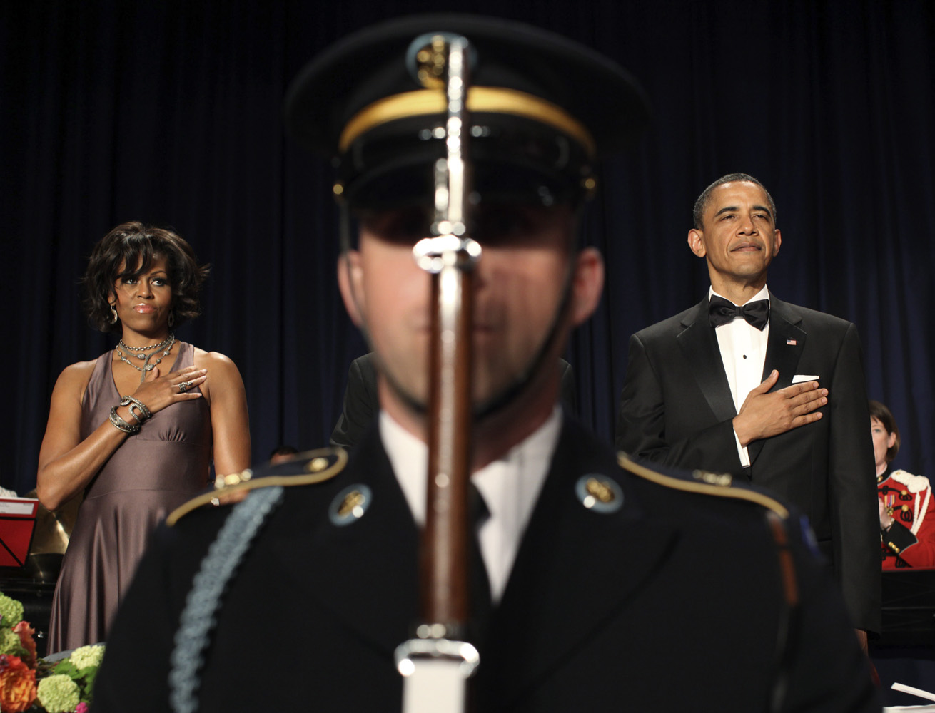 April 30, 2011. U.S. President Barack Obama and first lady Michelle Obama stand behind an honor guard soldier at the annual White House Correspondents Association Dinner at a hotel in Washington, D.C.
