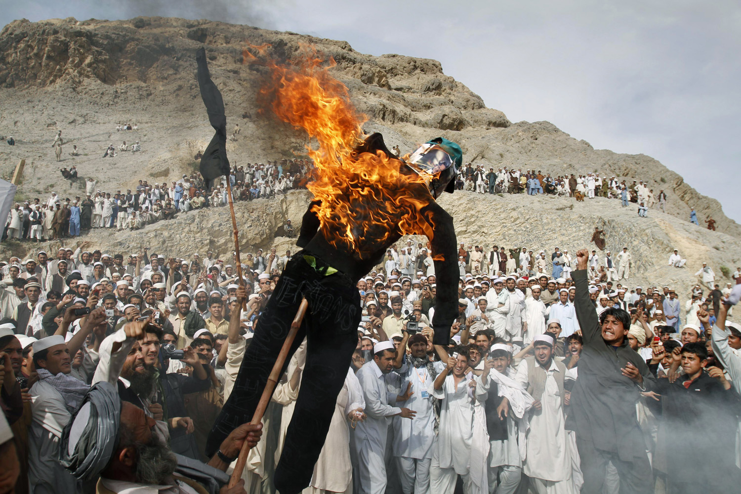 April 4, 2011. An Afghan protester holds a burning effigy of the American pastor, Terry Jones, during a demonstration in Shinwar, Nangarhar province, east of Kabul, Afghanistan.