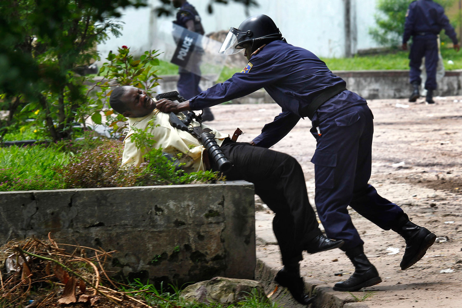 December 8, 2011. A supporter of Congolese opposition leader Etienne Tshisekedi is grabbed by a  Congolese riot police officer outside his candidate's headquarters in  Kinshasa, Democratic Republic of Congo.