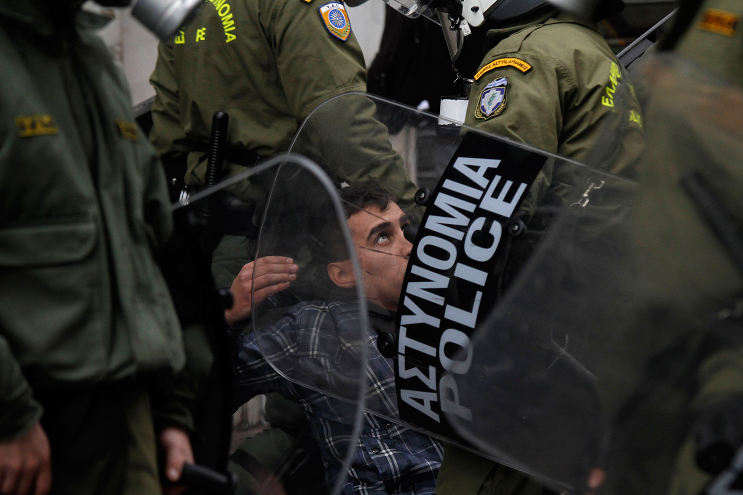 December 6, 2011. Riot police officers detain a protester during clashes in Athens. Protesting high school students hurled rocks and bottles during clashes clashed with police during a rally to mark the third anniversary of the fatal police shooting of a teenager in central Athens.
