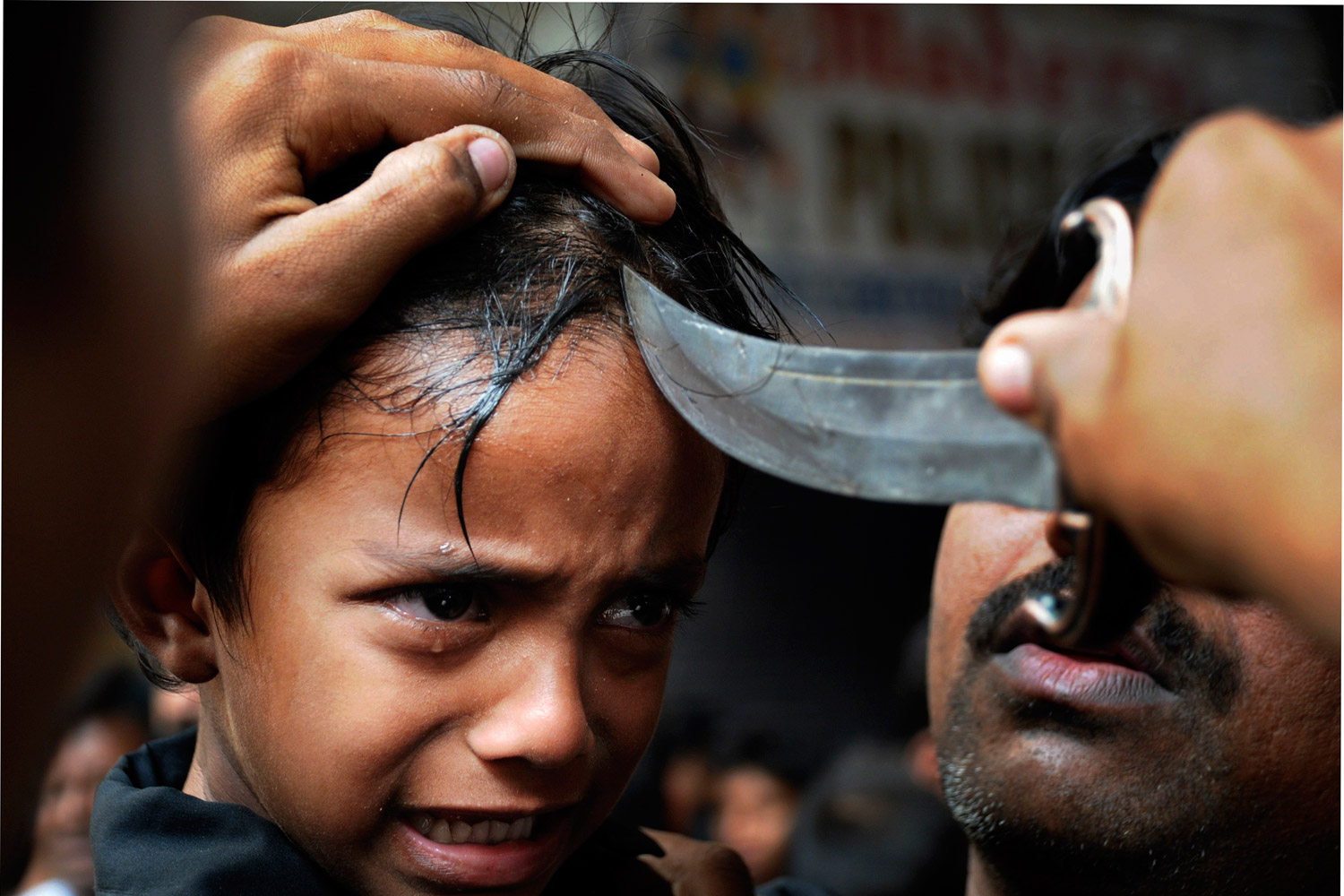 December 6, 2011. A young Indian Shiite Muslim cries as an elder makes a cut on his forehead with a knife during a procession to mark Ashura in Hyderabad, India. Ashura is the 10th day of Muharram, the first month of the Islamic calendar, observed around the world in remembrance of the martyrdom of Imam Hussein, the grandson of Prophet Mohammed.