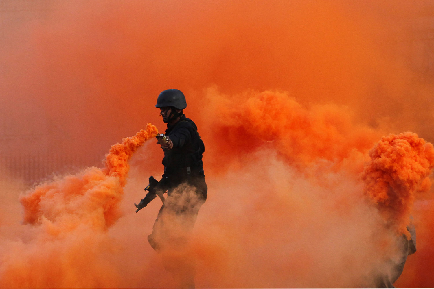 December 2, 2011. An Indian naval commando dispenses orange smoke during a dress rehearsal ahead of Navy Day in Mumbai, India.