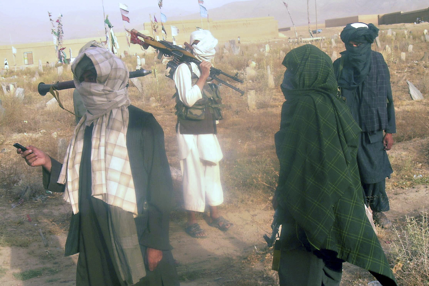 August 10, 2011. Fighters with Afghanistan's Taliban militia stand at a cemetery located west of Kabul, near the site where a CH-47 Chinook helicopter carrying US troops crashed, killing 38 personnel including 30 U.S. soldiers.