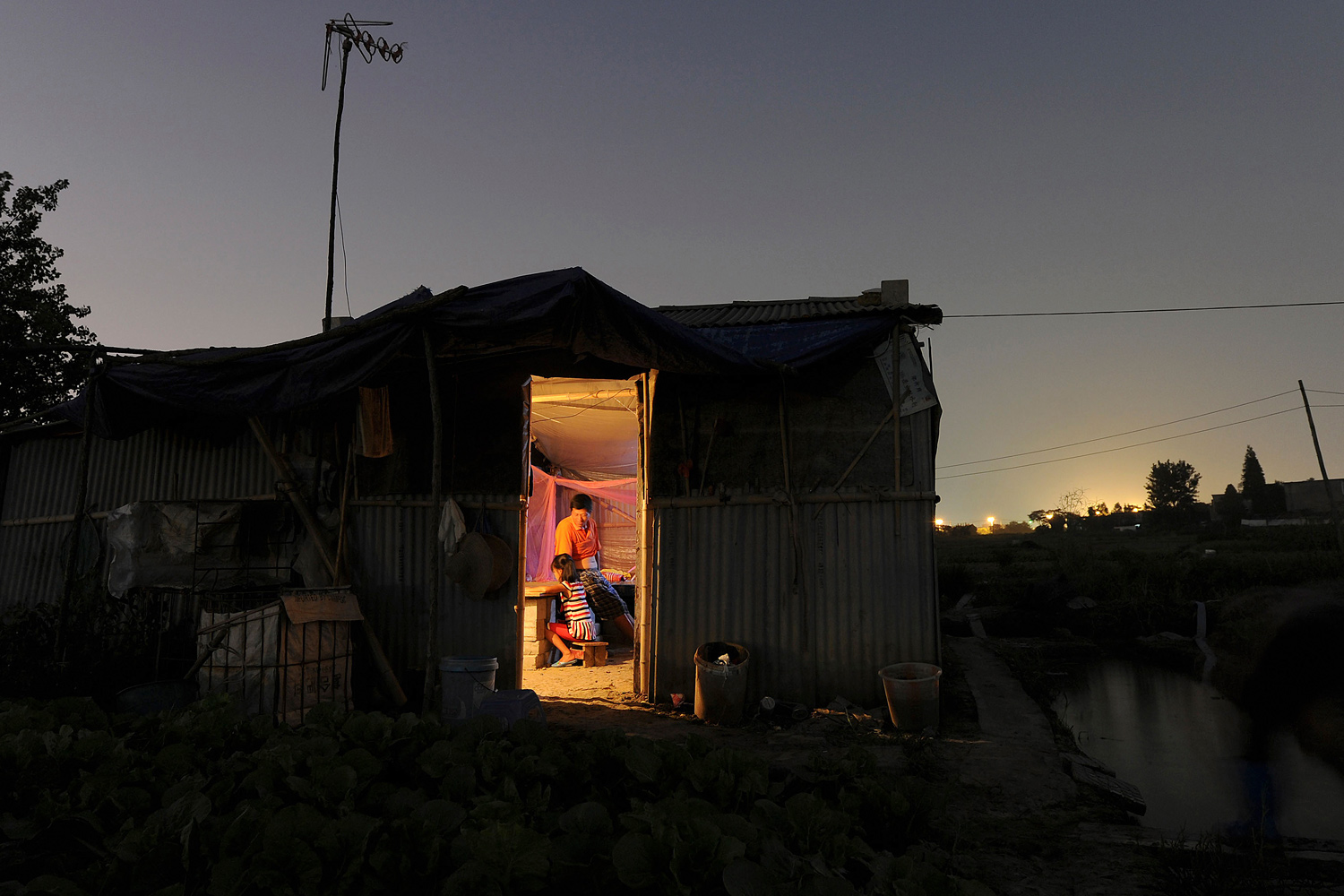 August 12, 2011. A farmer talks to his daughter in his wooden shed amid a vegetable farm on the outskirts of Hefei in China.
