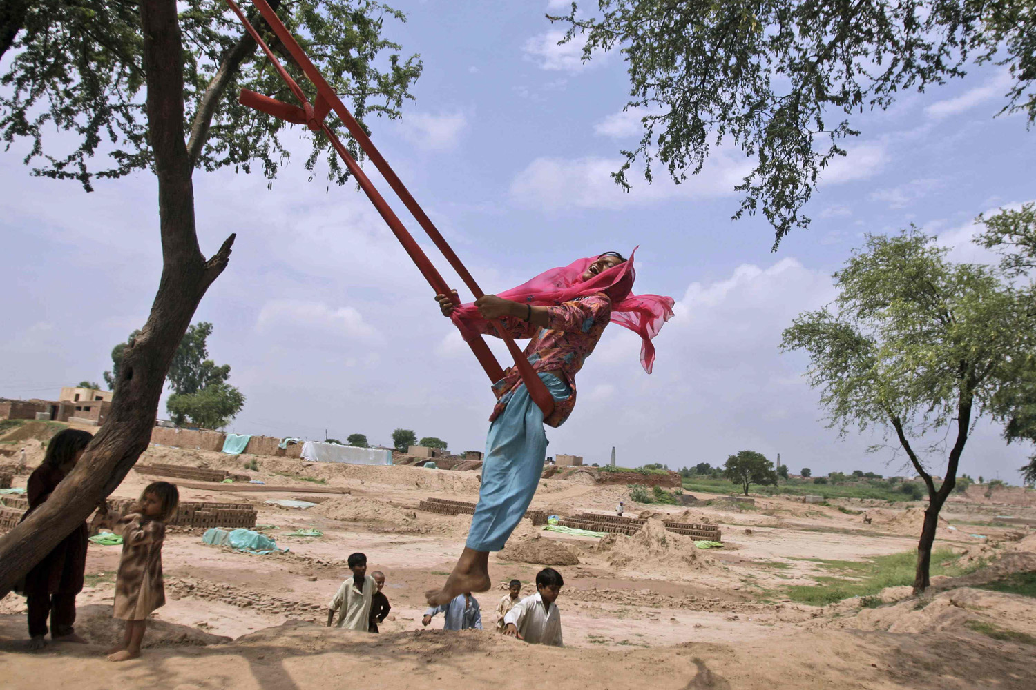 August 15, 2011. Pakistani Nargis Shah, 13, plays on a swing along with other children on the outskirts of Islamabad, Pakistan.