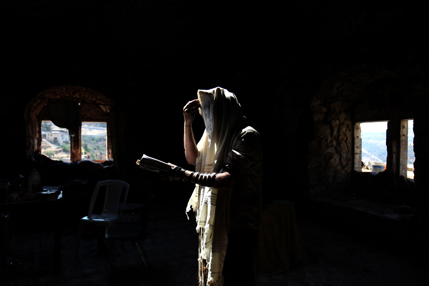 August 17, 2011. A Jewish Hasidic community member prays in a cave of an old Arab house where they live in Lifta, Jerusalem, Israel.