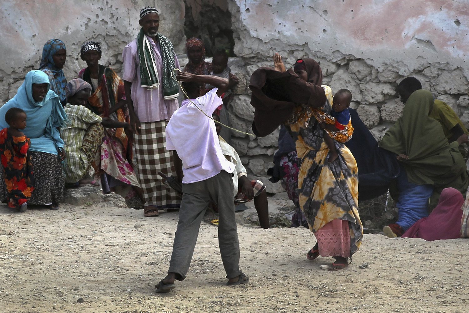 August 18, 2011. A security guard beats a woman for trying to enter a feeding center at a camp for Somalis displaced by drought and famine in Mogadishu, Somalia.